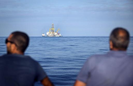 Dos personas observan el Rowan Renaissence, el barco con el que compañía petrolífera Repso ha realizado los sondeos petrolíferos al este de las islas de Lanzarote y Fuerteventura.