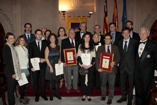 Foto de familia de los galardonados junto a los directivos de la Reial Acadèmia de Medicina de Balears y las autoridades que asistieron a la inauguración del curso.