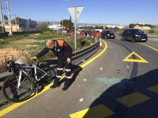 Un sanitario inspecciona la bici del herido, junto a los cristales rotos.