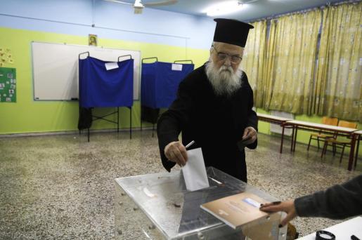 Un sacerdote ortodoxo deposita su voto en un colegio electoral de Grecia.