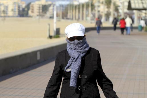 Una mujer pasea cerca de la Platja de Palma bien abrigada a causa del intenso frió.