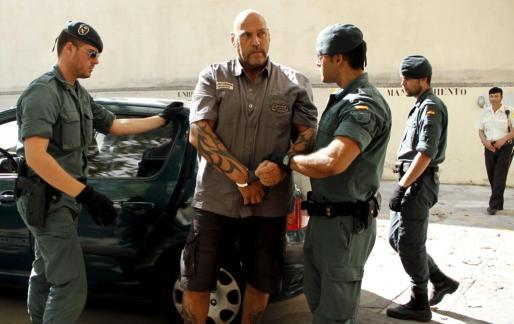 Dos agentes conducen el alemán Frank Hanebuth, líder de la rama alemana de los Ángeles del Infierno, a comisaría tras su detención.