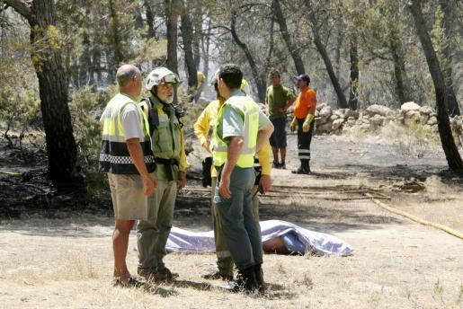 Miembros de los equipos que particparon ayer en tareas de extinción en Porto-Salè junto al cadáver.