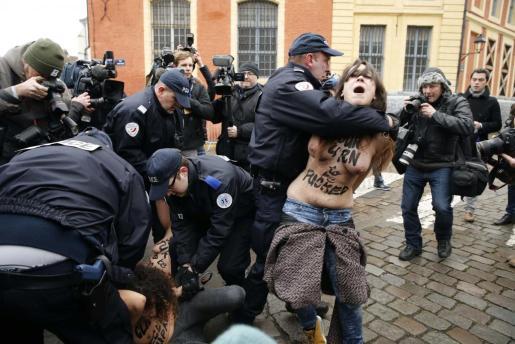 Las mujeres del colectivo Femen, que llevaban el torso con mensajes de protesta, han sido contenidas por la policía.
