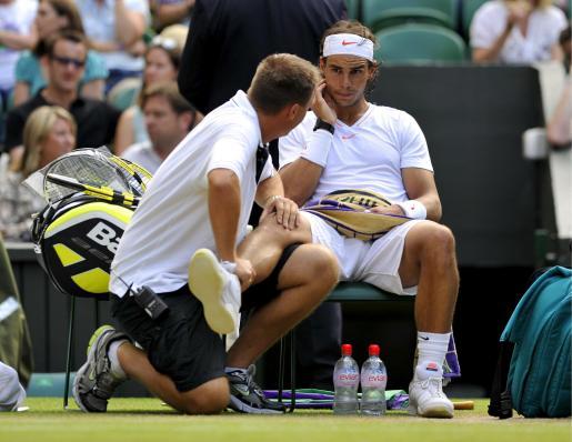 Rafael Nadal recibe la asistencia del fisioterapeuta de la ATP durante su partido de tercera ronda de Wimbledon ante el alemán Philipp Petzschner.