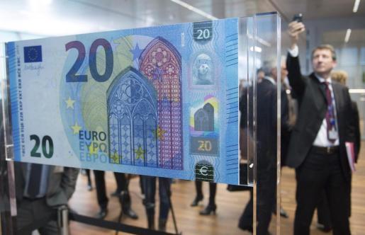 Un hombre fotografía el nuevo billete de 20 euros en el Banco Central Europeo (BCE), en Fráncfort (Alemania), este martes 24 de febrero de 2015. Draghi anunció que el nuevo billete entrará en circulación el 25 de noviembre y destacó que, hasta esa fecha, el Eurosistema habrá imprimido más de 4.300 millones de esos billetes.