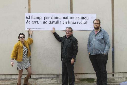 Laia Martínez, Joan Rotge y Miquel Ferrer colgando un cartel con palabras de Ramon Llull, durante la presentación de la Setmana del Llibre en Català.