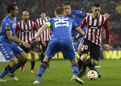 El delantero del Athletic Club Aritz Aduriz se escapa de los jugadores del Torino, durante el partido correspondiente a la vuelta de los dieciseisavos de final de la UEFA Europa Liga jugado esta noche en el estadio de San Mamés.