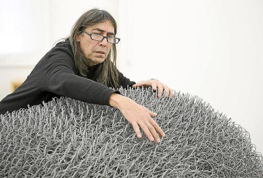 El artista Josep Maria Alcover, sobre una de sus obras que exhibe en Barcelona.