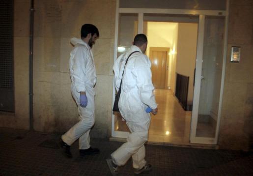 Dos agentes de la Policía Científica llegando a la vivienda en la que se encontró el cadáver calcinado.