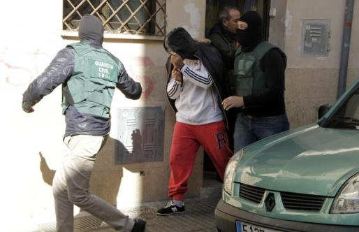 Uno de los detenidos, en el momento de ser conducido al vehículo policial en Palma.