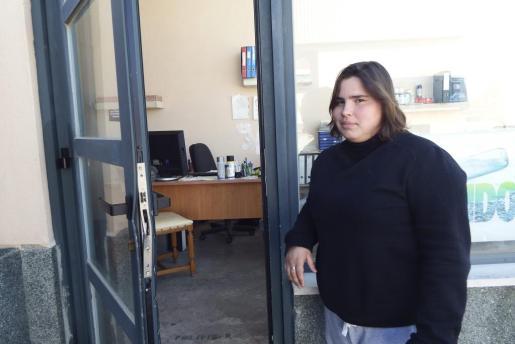 Una empleada junto a la puerta destrozada de una de las empresas asaltadas.