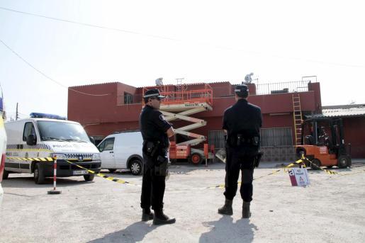 Efectivos policiales vigilan mientras los operarios comienzan el desmantelamiento de la vivienda.
