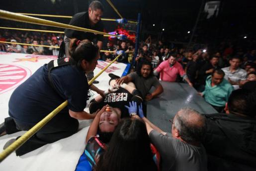 El luchador mexicano Pedro 'Perro' Aguayo Jr. recibe atención tras recibir una patada voladora de su rival, Rey Misterio, durante una batalla arriba del cuadrilátero.