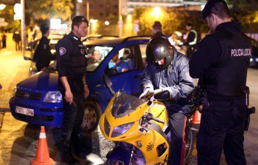 Dos agentes del GAP de la Policía Local de Palma revisan la documentación de un motorista.