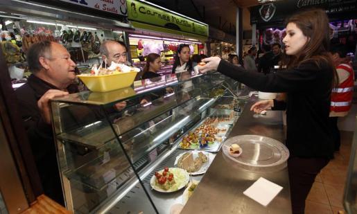 Un gran número de personas que acudieron ayer al Mercat Nou a realizar sus compras, se encontraron sin saberlo, con todo un escaparate de sabrosas propuestas culinarias. Foto: DANIEL ESPINOSA