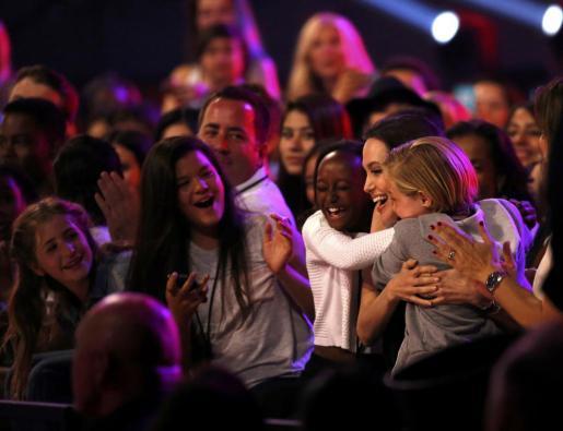 La actriz Angelina Jolie, abraza a sus hijas Vivienne y Shiloh tras ganar el premio a la mejor villana en los Kids' Choice Awards.
