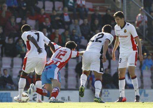 Un jugador del Lugo cae ante la presencia de Pereira, Yuste y Cendrós.