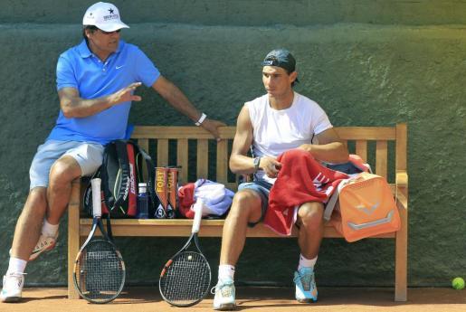 El tenista manacorí Rafa Nadal junto a su entrenador, Toni Nadal (i), durante el entrenamiento que ha realizado este martes en las instalaciones del Real Club de Tenis, donde este miércoles debutará en el Barcelona Open Banc Sabadell-Trofeo Conde de Godó.