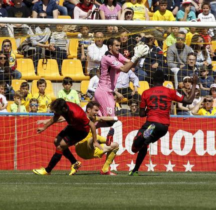 Cabrero, portero del Mallorca, atrapa la pelota por la que luchan sus compañeros Company y Kasim con un jugador del Alcorcón.