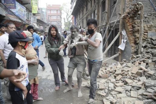 Dos jóvenes ayudan a un hombre tras quedar sepultado por los escombros.