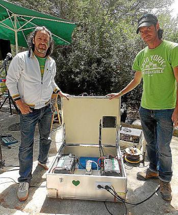 Dos miembros de Casita Verde enseñan las baterías de energía solar con las que dieron electricidad a la megafonía del evento.