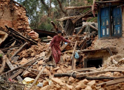 Una mujer trata de moverse entre los escombros dejados por el terremoto que sacudió el este sábado el Nepal.
