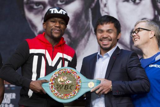 Floyd Mayweather Jr. (izquierda) y Manny Pacquiao (derecha) posan junto al cinturón.