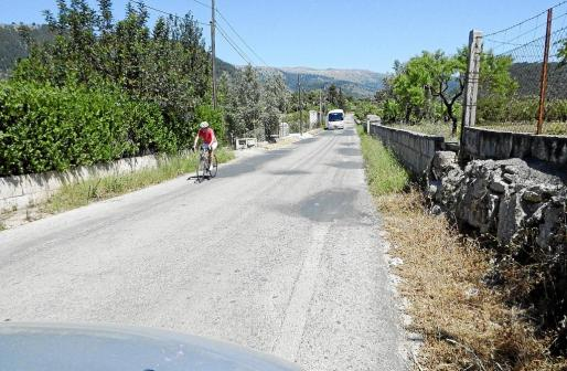 Ciclistas, autocares y baches parcheados definen una carretera que transcurre por una zona de gran valor paisajístico.
