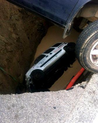Fotografía facilitada por la Policía Local de Las Palmas de Gran Canaria, del coche de un hombre que se ha quedado atrapado tras ser engullido su vehículo por un socavón en la calle Artenara, en un polígono industrial de Las Palmas de Gran Canaria.