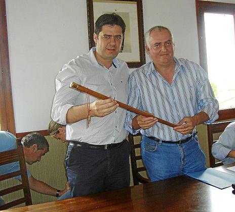 Jaume Bauzà, recogiendo la vara de la mano de Guillem Mas.