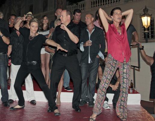 El príncipe Alberto de Mónaco, su prometida y la princesa Carolina bailando en un concierto de rock.