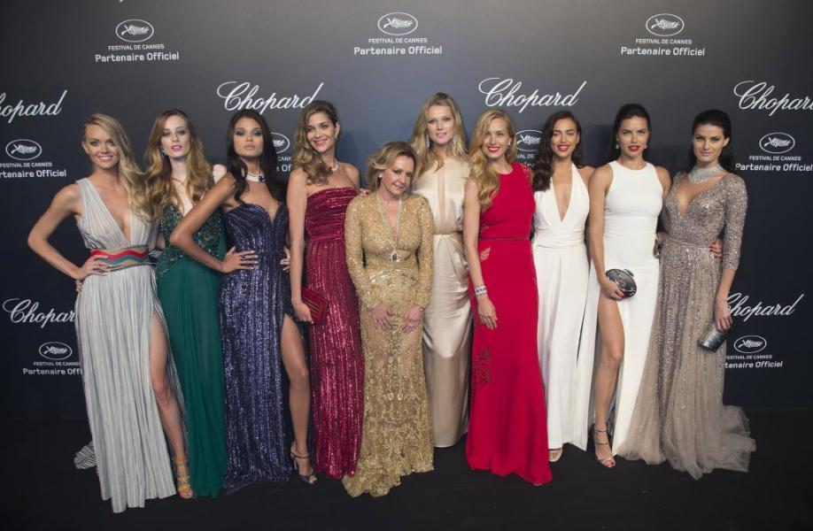 Models and Caroline Scheufele, Artistic Director and Co-President of Chopard pose during a photocall ahead of the Chopard Gold P