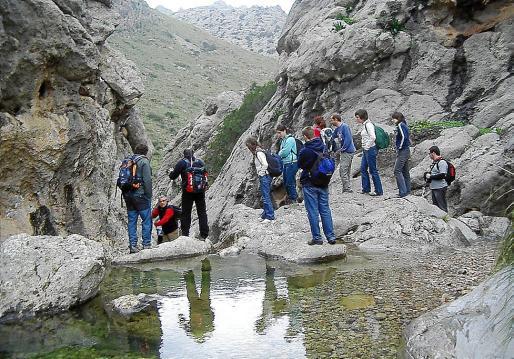 Un grupo de excursionistas atraviesa un torrente de la Serra de Tramuntana.