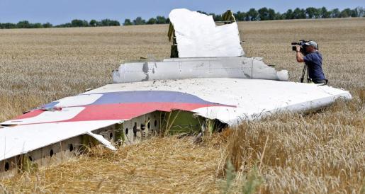 Fotografía de archivo fechada el 20 de julio de 2014 en la que aparece un operario de cámara mientras graba un detalle de los restos del vuelo MH17 de Malaysia Airlines en el lugar de la caída del avión, cerca de Grabovo, a 100 km de Donetsk (Ucrania).