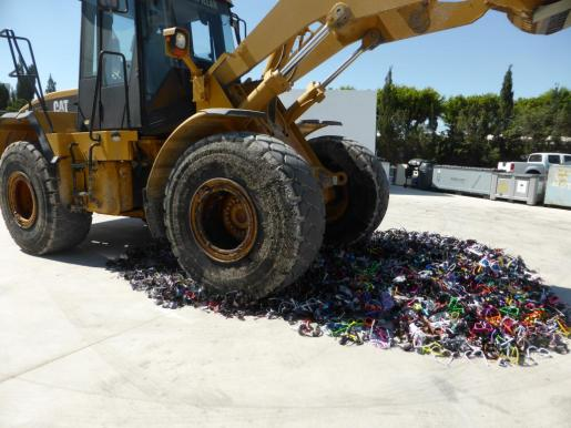 Momento en que la excavadora destruye el material intervenido por la Policía Local.