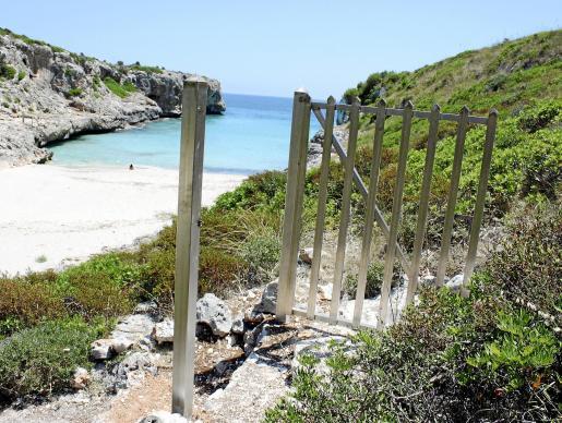 Las escaleras que llevan a la playa virgen de Cala Sequer, con una barrera.