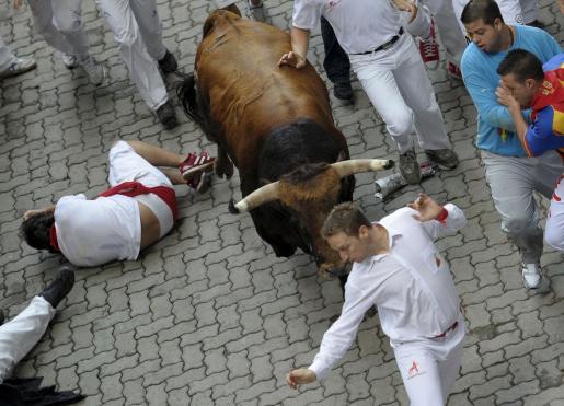 Varios mozos pasan un momento de apuro ante las astas de un toro de la ganadería gaditana de Fuente Ymbro.
