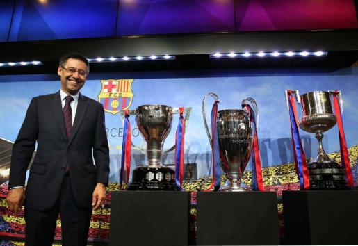 El presidente del FC Barcelona, Josep María Bartomeu, posa con los trofeos de la Liga, Liga de Campeones y Copa del Rey al finalizar su comparecencia.