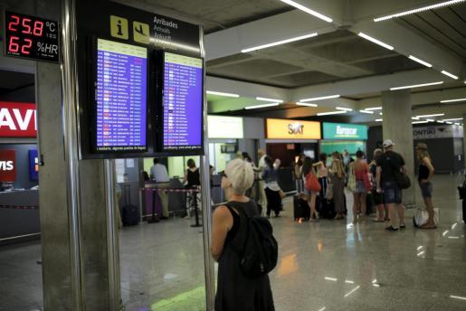 Una viajera revisa los horarios de los vuelos en unas pantallas del aeropuerto de Son Sant Joan durante la segunda jornada de huelga de los controladores aéreos.