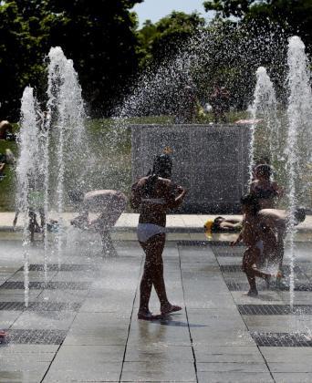 Niños y mayores tratando de refrescarse en unas fuentes en uno de los días que más ha apretado el calor.