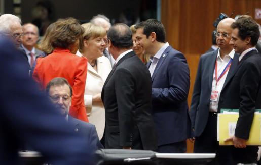 El primer ministro griego Alexis Tsipras (3-D) habla con la canciller alemana, Angela Merkel (3-L) y el presidente francés, Francois Hollande (C) al inicio de la cumbre de líderes de la eurozona 'en la crisis griega en la sede del Consejo Europeo en Bruselas. En primer plano, sentado, Mariano Rajoy.
