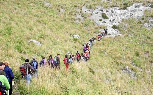 Imagen de un extenso grupo de excursionistas transita por uno de los múltiples caminos de la Serra de Tramuntana.