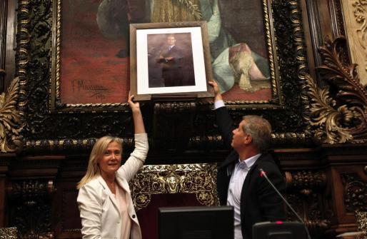 Los concejales del PPC, Alberto Fernández Díaz y Ángeles Esteller, colocan este viernes una fotografía de Don Felipe en la repisa del salón de plenos donde hasta ayer estaba el busto de Don Juan Carlos.