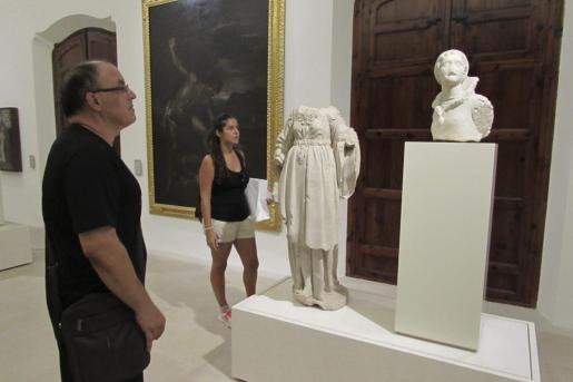 Dos visitantes del Museu de Mallorca contemplan unas esculturas.