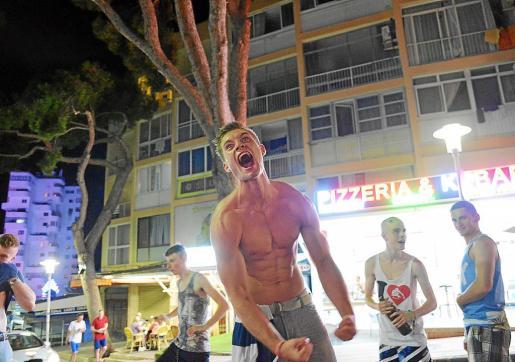 Un joven eufórico hace gala de su físiico ante sus amigos y demás turistas.