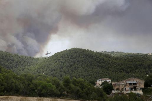 Un helicóptero trabaja cerca de varias viviendas para combatir de Ódena.