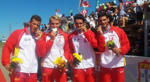 El mallorquín Marcus Cooper, el segunda por la izquierda, muerde la medalla de oro junto con sus compañeros del K4.