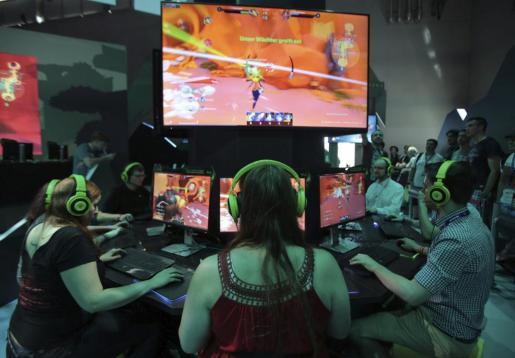 """Visitantes prueban el videojuego Gigantic durante la """"Gamescom 2015"""", la principal feria de juegos interactivos que tiene lugar en Colonia, Alemania, este miércoles 5 de agosto de 2015."""
