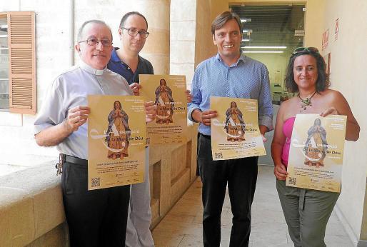 Antoni Vera, Biel Carrió, Francesc Miralles y Kika Coll muestran el cartel que anuncia la festividad de la Mare de Déu d'Agost, una tradición religiosa y cultural muy arraigada.